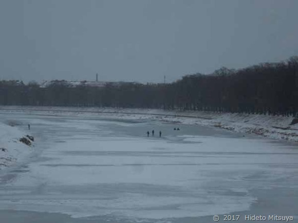 凍り付いた川とそこを渡る人